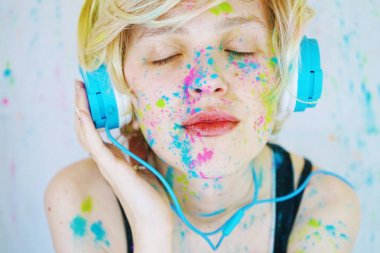 Portrait of young blonde woman with painted face in blue headphones listening to music on background