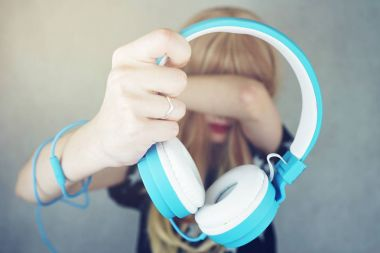 close-up of woman hand holding blue headphones on background