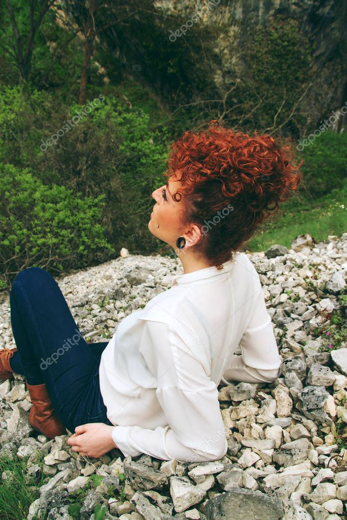 beautiful redhead woman posing sitting on nature background
