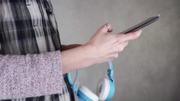 close-up of female hands holding and using mobile phone on grey wall background