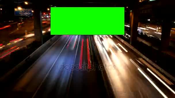 Reklamní zelená obrazovka s provozem v noci.