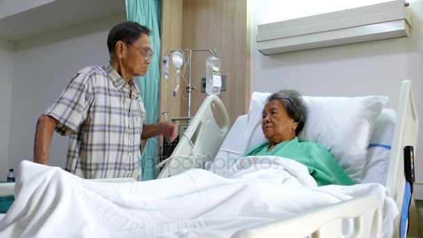 Senior man as he visits wife in hospital room.