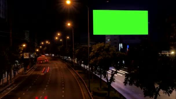Zelená obrazovka prázdná reklama Billboard vedle silnice s provozem v noci, pro reklamu, časová prodleva