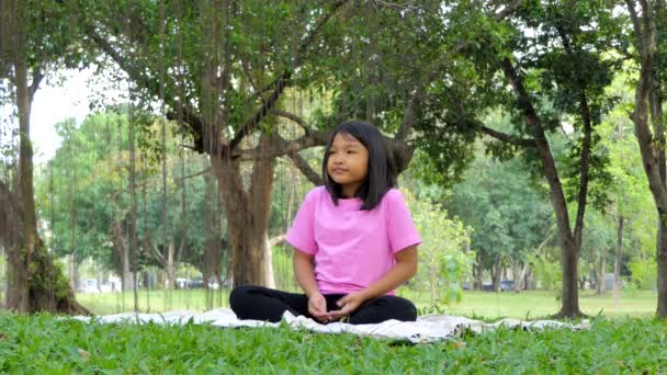Asian girl meditating practicing yoga under a tree in public park.