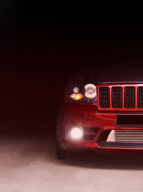 Kharkov, Ukraine. January 3. Part of the Jeep Grand Cherokee SRT8 in the shadows with glowing lights in low light. Brutal off-road car in the shade. Editorial photo