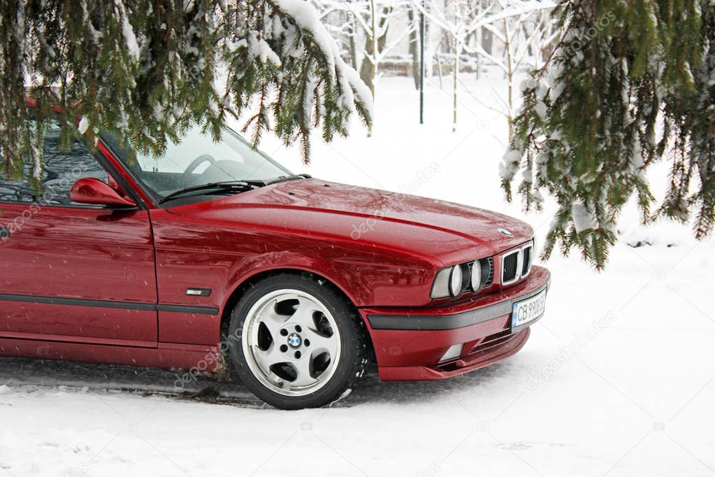 Kiev, Ukraine - December 22, 2017: BMW 520 (E34) in the winter forest. Red BMW in a beautiful forest. Nature. Snow.