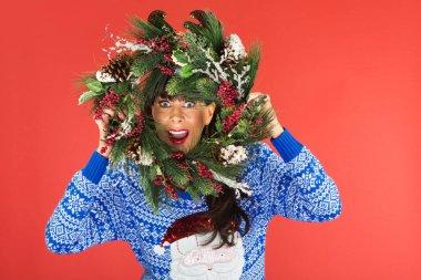 Woman looking through Christmas wreath