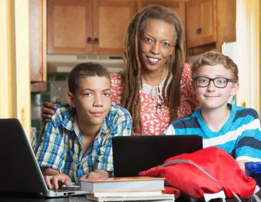 Mother with son and friend doing homework