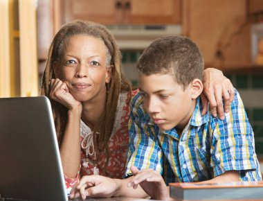 Mother helps teenage son with homework in kitchen