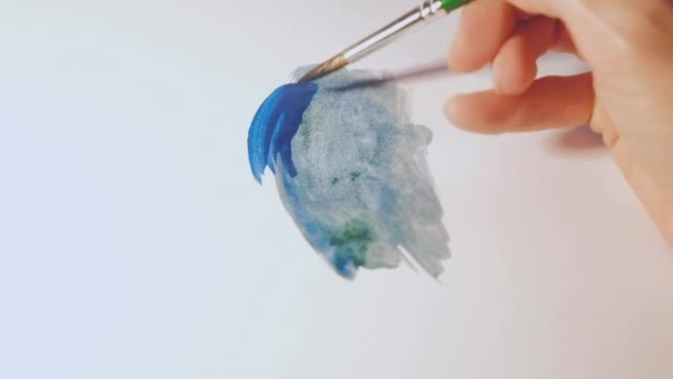 A watercolor palette of colors and a womans hand drawing an abstract drawing with a brush.