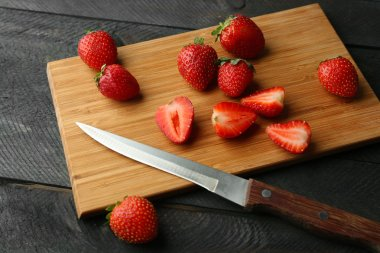 Ripe strawberries and knife on cutting board and dark wooden background