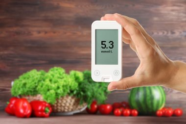 Male hand holding glucometer with fresh vegetables and greens on wooden background. Diabetes concept