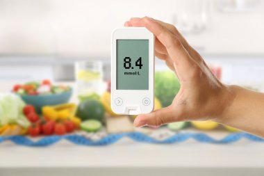 Male hand holding glucometer with fresh fruits and vegetables on table. Diabetes concept