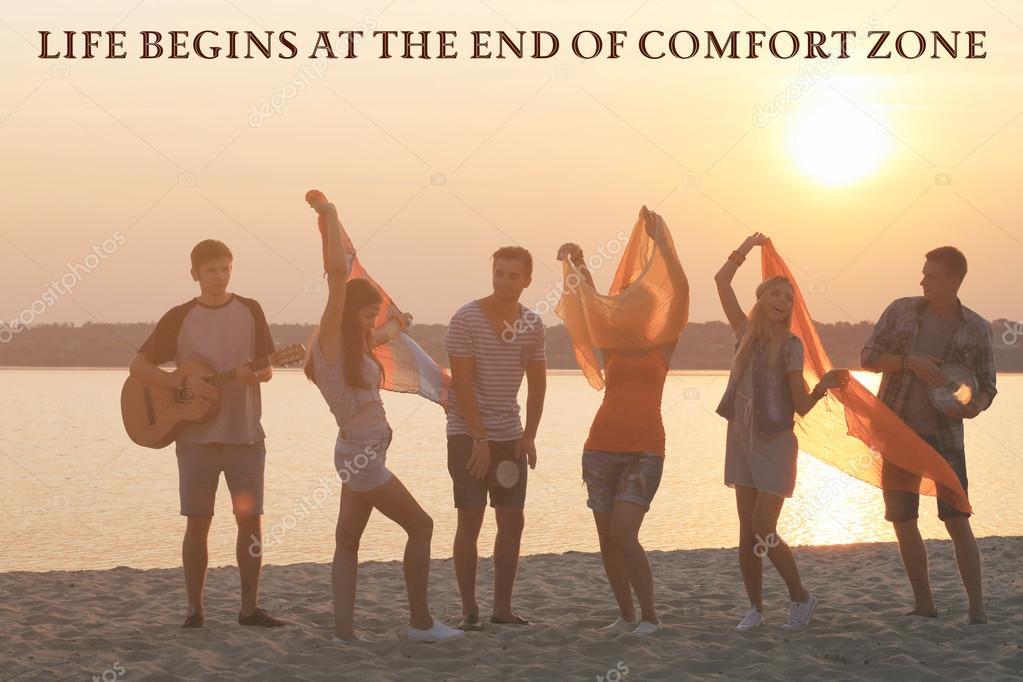 Comfort zone concept, Joyful friends having fun on shore at sunset outdoors