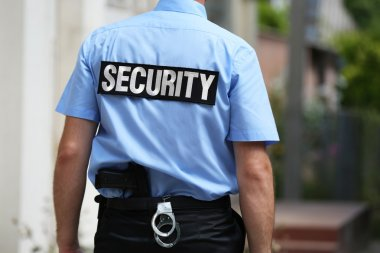 Male security guard standing back outdoors