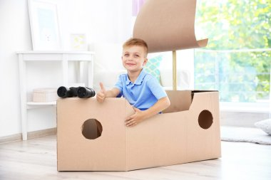 Little boy playing with cardboard ship indoors
