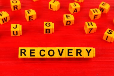 Word recovery made with yellow plastic blocks on wooden background