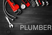 Photo Plumbing concept. Plumber tools on a gray wooden background