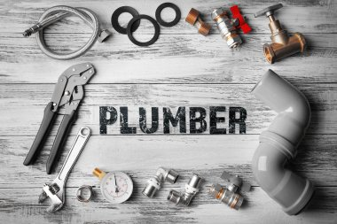 Plumbing concept. Plumber tools frame on wooden structure background