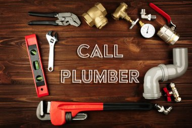 Call Plumber. Plumber tools frame on wooden background