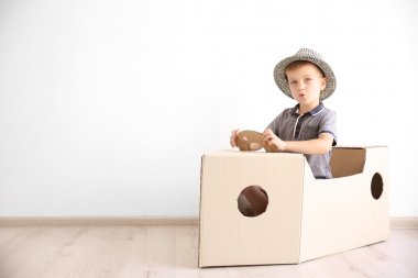 Little boy playing with cardboard ship