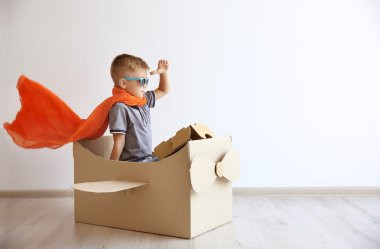 Little boy playing with cardboard airplane