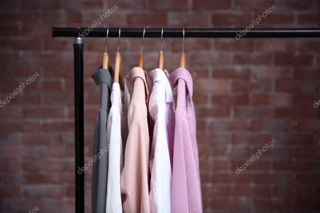 Bastone Appendiabiti.Priorita Bassa Del Muro Di Appendini Con Camicie Donne Su Bastone