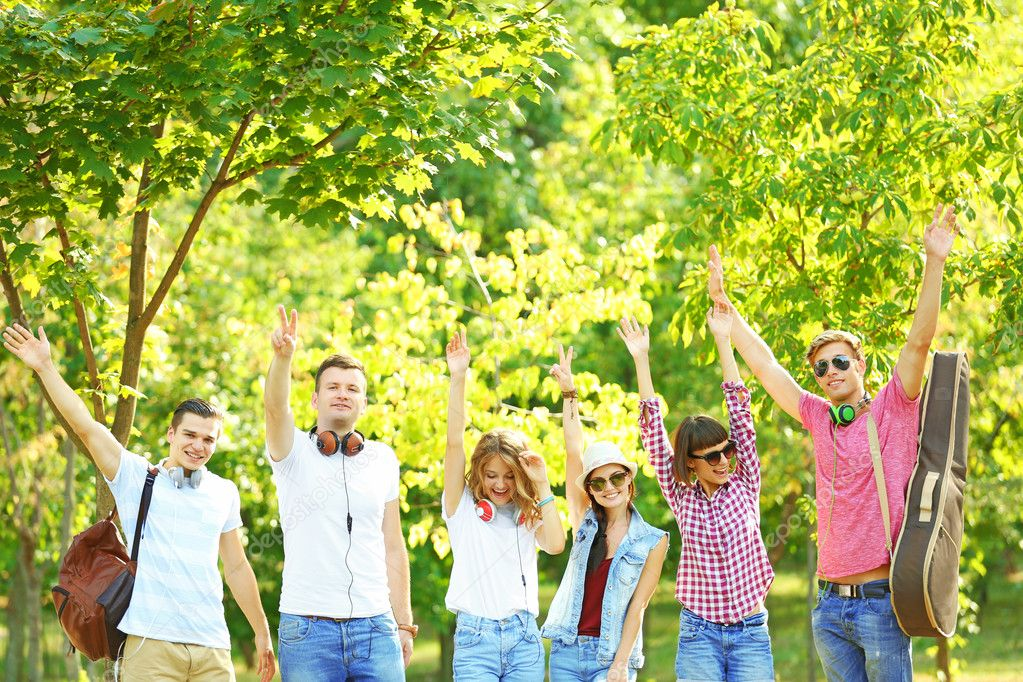 Happy young friends standing with raised hands on park