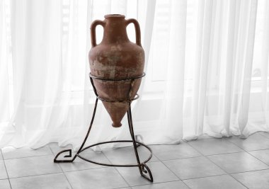 Ancient amphora on stand on curtain background