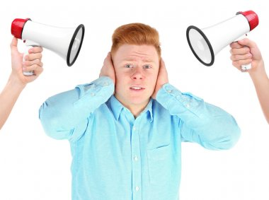 Young stressed man closing ears cause of loud noise from megaphones on white background