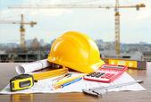 Konstrukční výkresy s nástroji a helmu na stavební konstrukce na pozadí