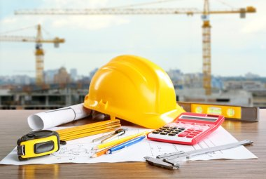 Construction blueprints with tools and helmet on building construction background