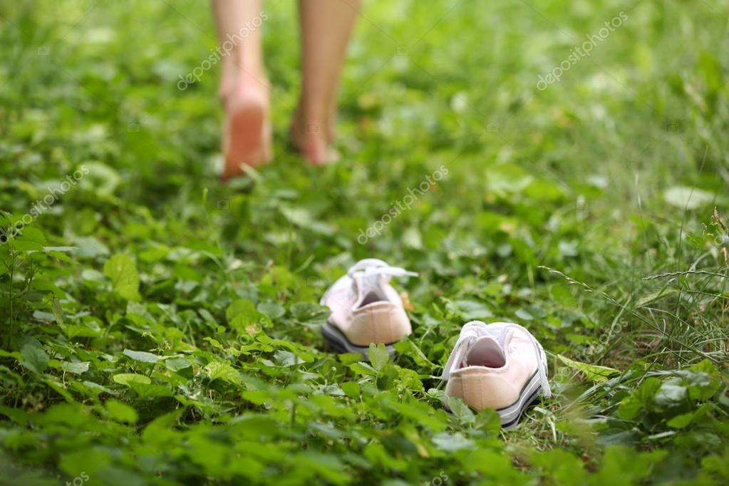 Female legs on green grass