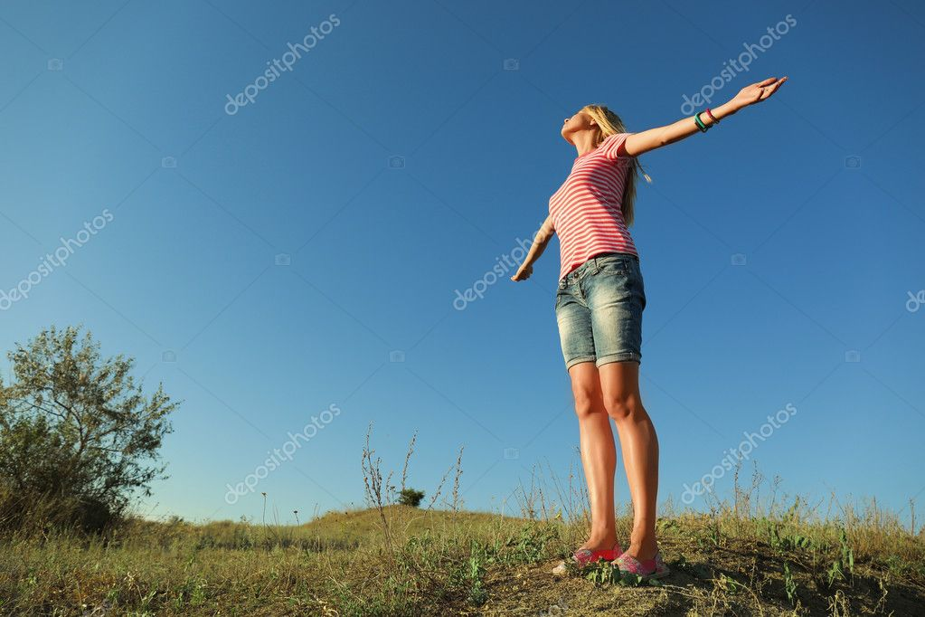 Happy young woman on blue sky background