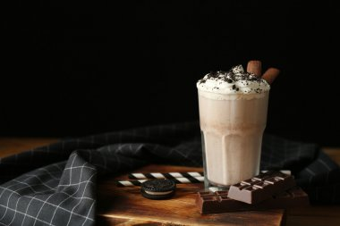 Delicious milkshake with chocolate and cookies on wooden table closeup