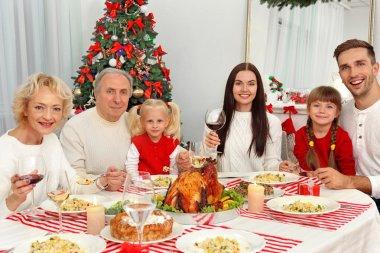 Happy family having Christmas dinner in living room