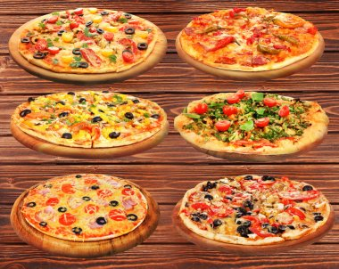 Set of delicious pizzas on wooden background.