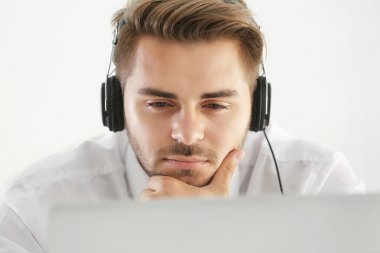 Handsome young man listening to music with headphones and working on laptop at office