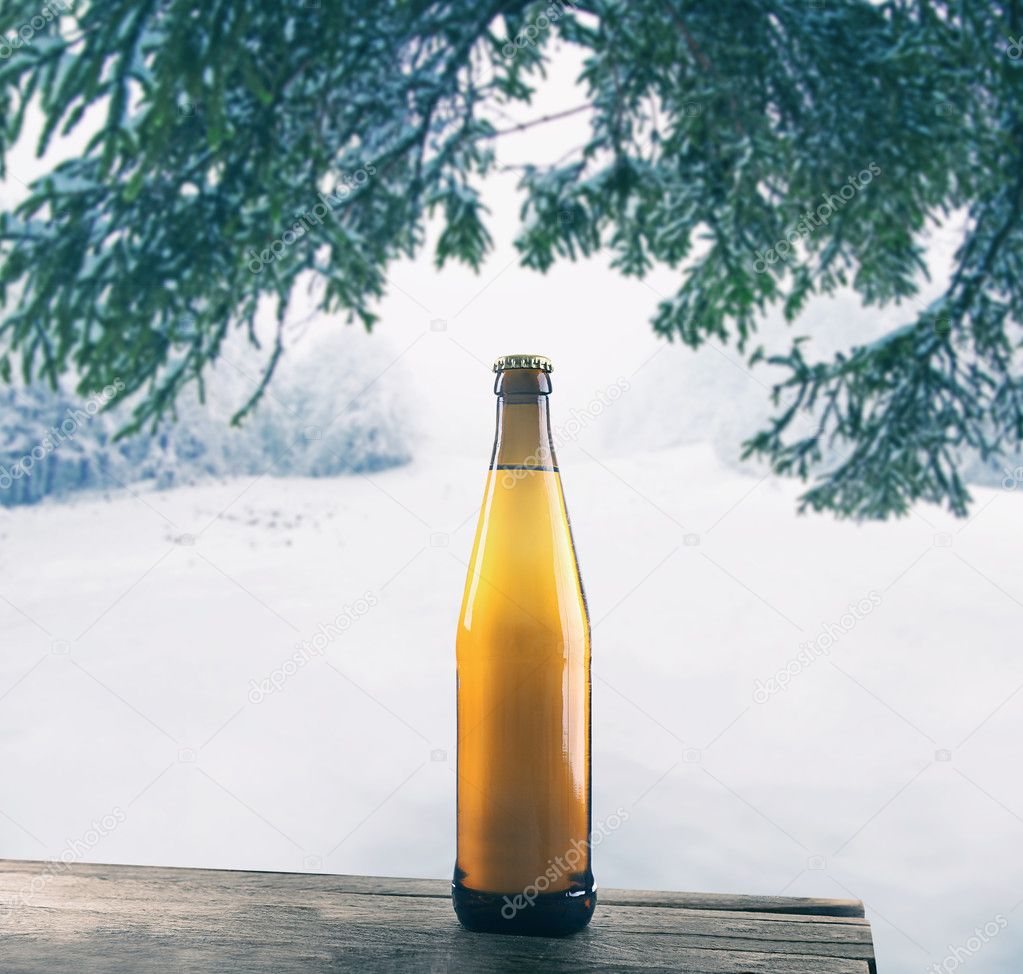 Glass bottle of beer on wooden table against winter nature background.
