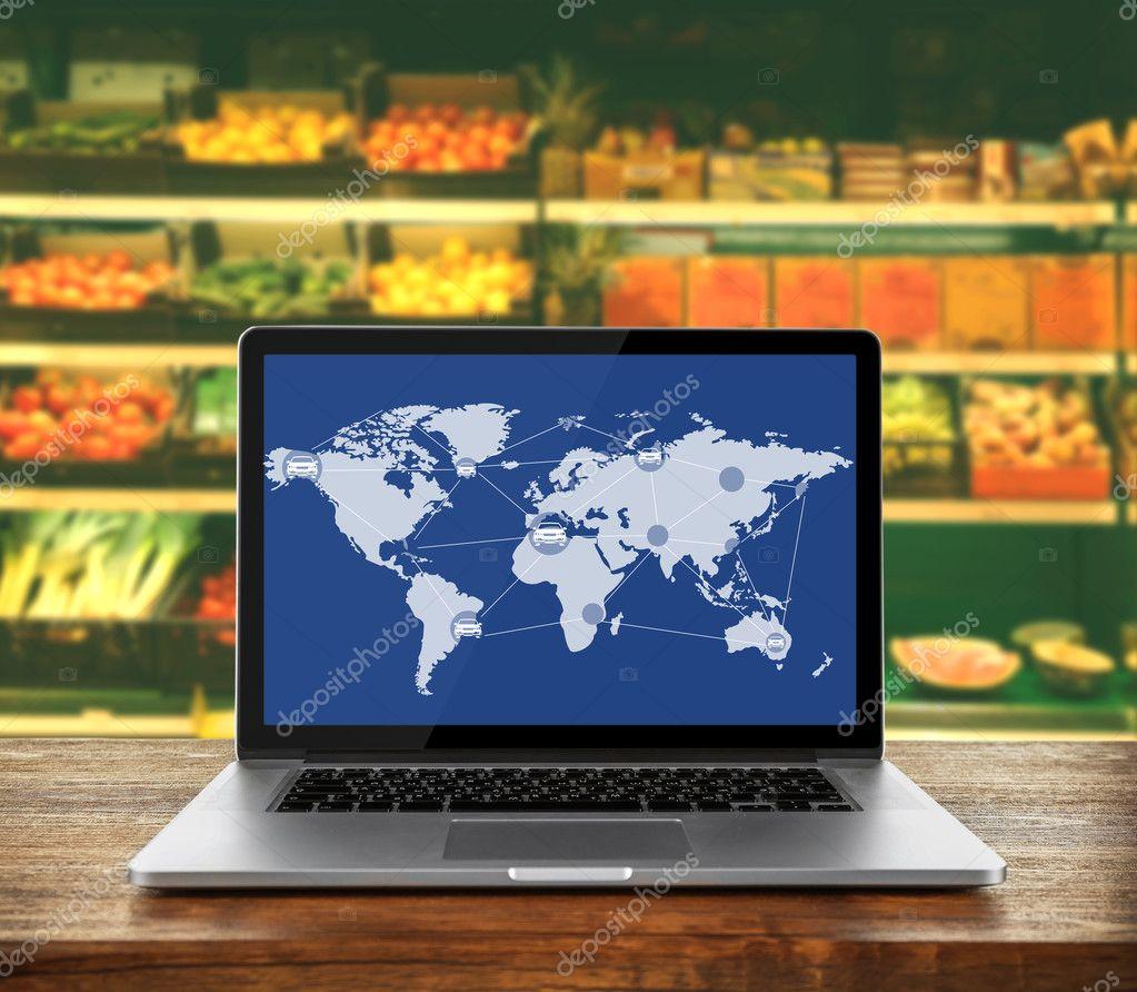 laptop op houten tafel tegen supermarkt interieur achtergrond wereldwijde logistieke vervoersnetwerk op het scherm groothandel en retail concept foto