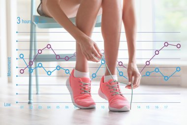 Woman tying shoelace at home. Graphic of training results. Health care and sport concept.