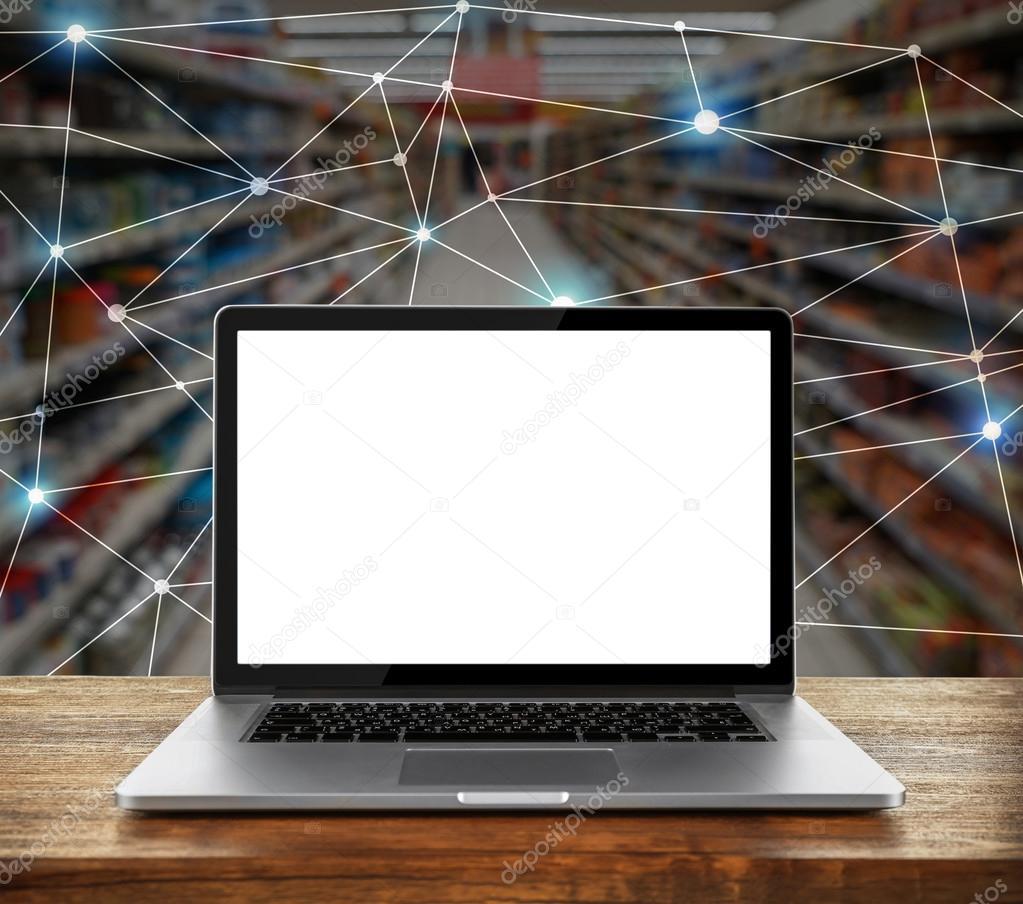 laptop met leeg scherm op houten tafel tegen supermarkt interieur achtergrond groothandel en retail concept