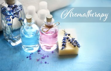 Spa composition with essential oils and lavender, closeup. Word AROMATHERAPY on background. Spa beauty concept.