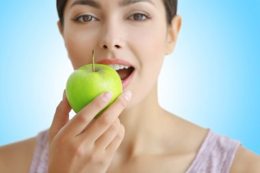 Young woman eating green apple, closeup. Dentist concept.