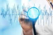 Elettrocardiogramma e mano femminile con stathoscope, primo piano. Concetto di cardiologia.