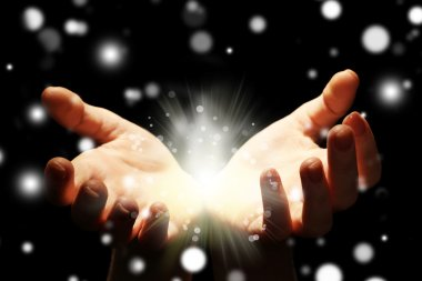 Female hands holding light in dark, closeup. Snowy effect, Christmas miracle concept.