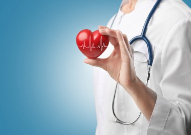 Cardiologist holding red heart with electrocardiogram. Cardiology concept.