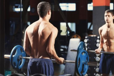 Athletic man training with barbell in gym