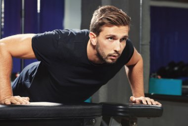 Handsome man doing push ups in gym