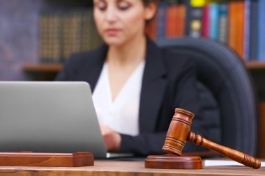 Brown gavel on wooden table and female lawyer on background, close up view